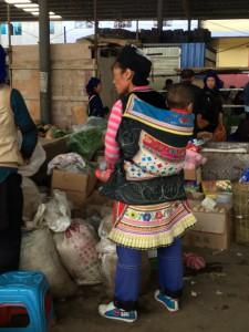 I de fattigare delarna av Kina arbetar man ofta med sina barn på ryggen.